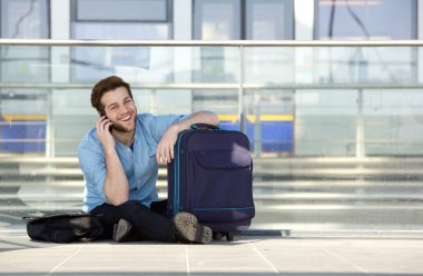 Happy traveler waiting at station and talking on cell phone