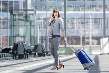 Smiling business woman walking with bag and mobile phone