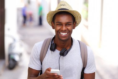 happy traveler walking in town with mobile phone