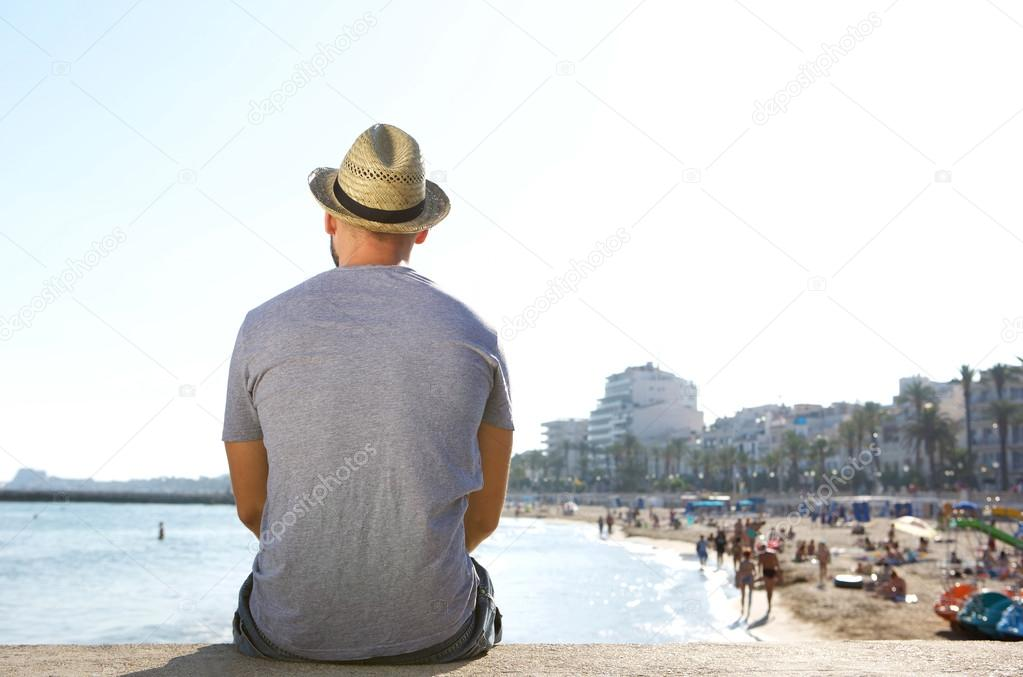 Portrait from behind of a man sitting alone looking at the beach