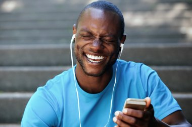 Laughing man holding cell phone listening with earphones