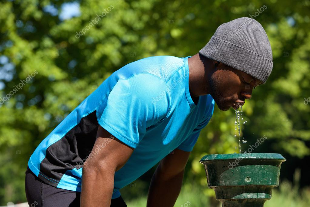 young black man drinking water from a water fountain u2014 stock photo