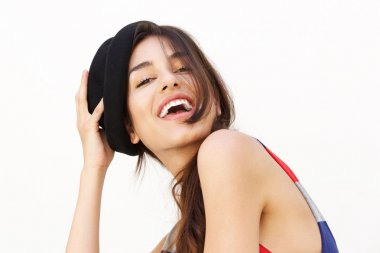 Cute girl with hat laughing against white background