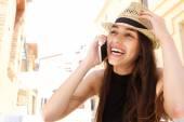 lachende junge Frau hört Handy