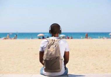 Man sitting by the beach listening to music on headphones