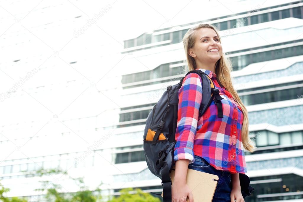 Estudiante Sonriente Caminando Fuera Con Bolso Y Libro