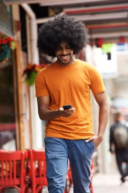 Smiling man walking with cellphone in town