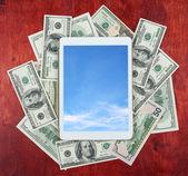 A tábla-pc elhelyezett pénz dollár és fa háttér, felhő-ég a képernyőn, üzleti koncepció és információk makett