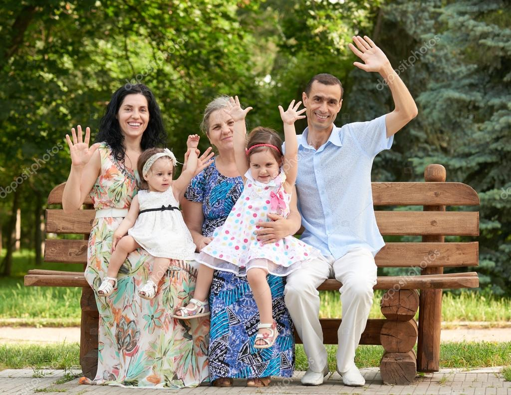 Admirable Big Family Sit On Wooden Bench In City Park And Waving Bralicious Painted Fabric Chair Ideas Braliciousco