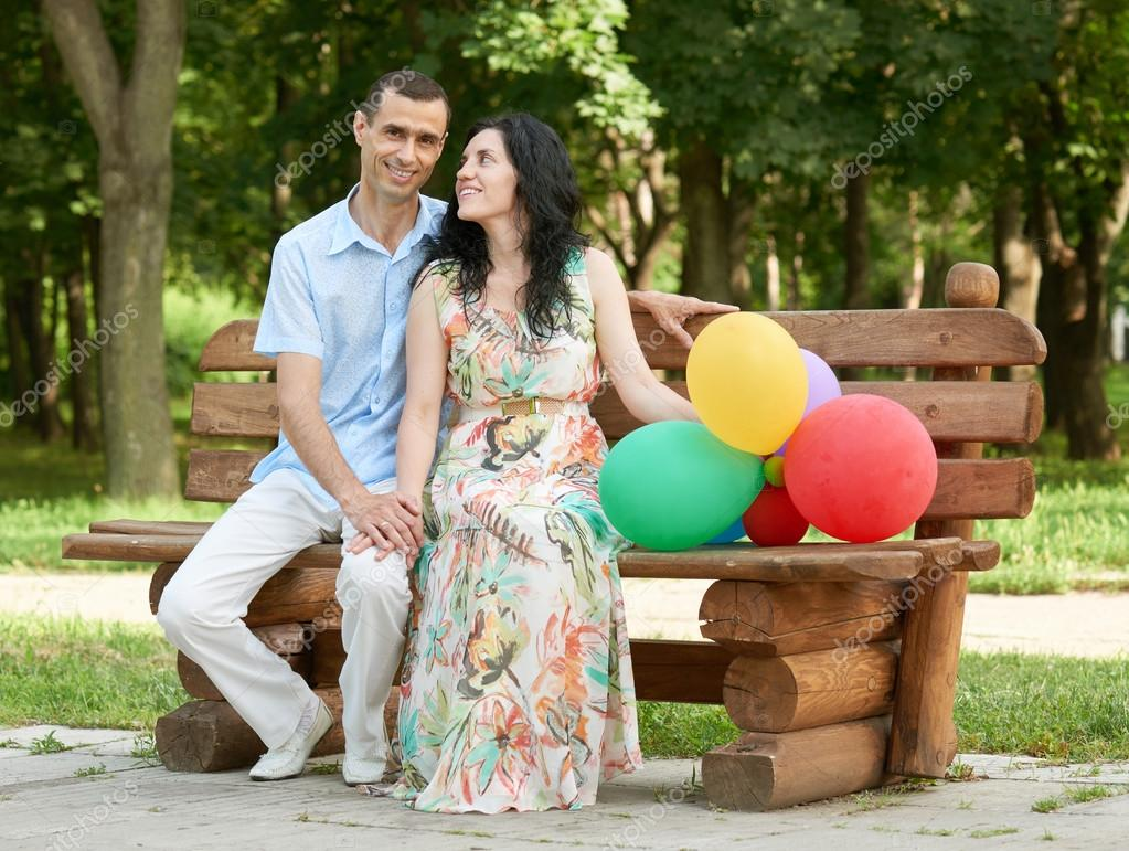 Happy Romantic Couple With Balloon Sit On Bench In City Park And
