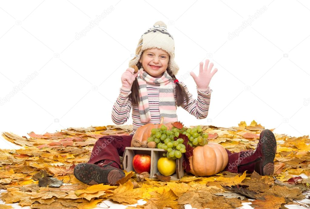 girl with fruits and vegetables on autumn leaves
