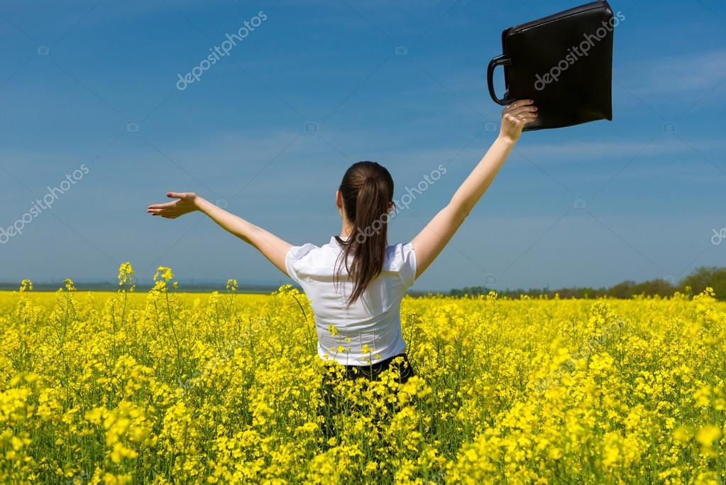 girl with briefcase on yellow flower field