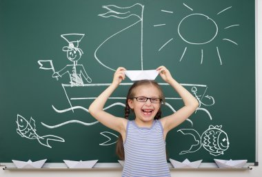 girl with origami ship drawing on school board