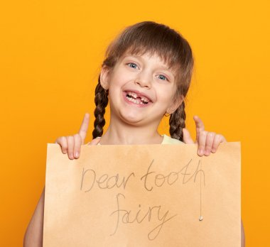 lost tooth girl portrait, studio shoot on yellow background