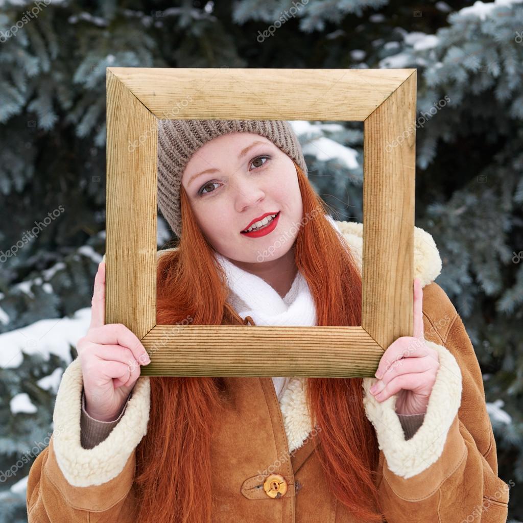 Mädchen-Portrait in hölzernen Bilderrahmen auf Wintersaison. Das ...