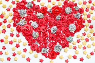 Roses from paper dacorated in hearth shape among star background