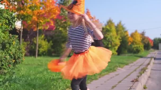 4k. Halloween kids. little blonde girl in witch costume having fun dancing outdoors. Spinning , rotation, Ready for the holiday