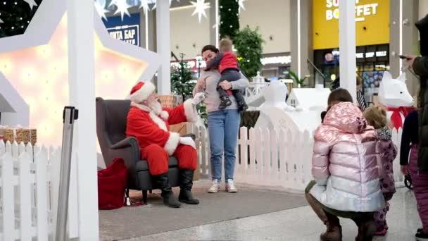 Der Weihnachtsmann im Gespräch mit Kindern in einem Einkaufszentrum. Weihnachtsgeschäft und Wünsche. Zeitlupe. 13dec2019 Sankt-Petersburg Russland