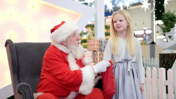 Der Weihnachtsmann plaudert und spielt Überraschungsspiele mit Kindern in der Shopping Mall. Weihnachtsgeschäft und Wünsche