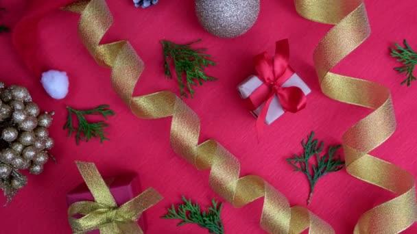 Otáčení vánočního pozadí. Dárkové krabice s červenou zlatou stuhou vánoční ozdoby, vánoční koule na červenou. Otočení o 360 stupňů. Koncepce prodeje, nakupování a oslavy