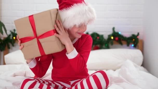 Chlapec třese dárkovou krabicí, aby zjistil, co je uvnitř. Dítě ve vánočním klobouku a pyžamu. Splňující přání, sny a překvapení pro děti