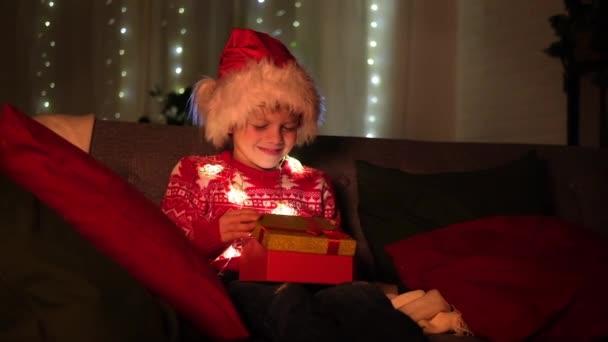 Vánoční zázraky. Chlapec v klobouku Santa Clause otevírá dárek doma. Splňující přání, sny a překvapení pro děti.