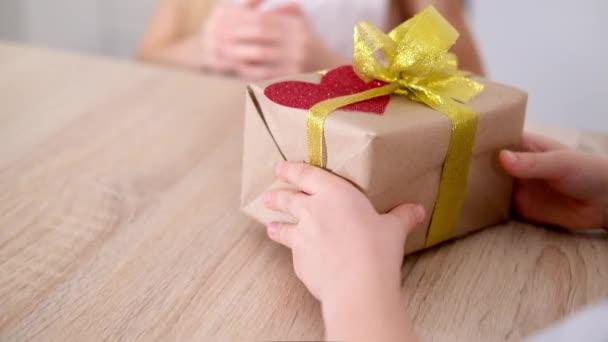 Chlapec dává své milované dívce na Valentýna dárkovou krabici. Šťastně se usmívající blonďaté děti slaví Valentýna. Zpomalený pohyb.