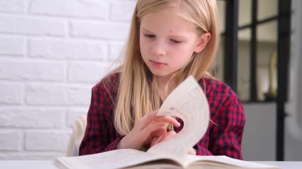 4k szőke iskoláslány, aki otthon tanul és házi feladatot csinál. Képzési könyvek és jegyzetfüzetek az asztalon. Távolsági tanulás online oktatás.