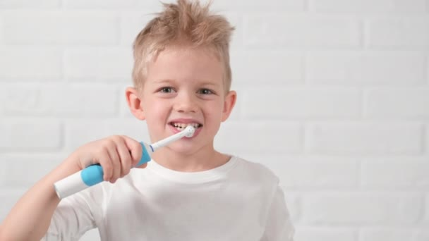 Portrait happy smiling child kid boy brushing teeth with electric toothbrush on white brick background. Health care, dental hygiene
