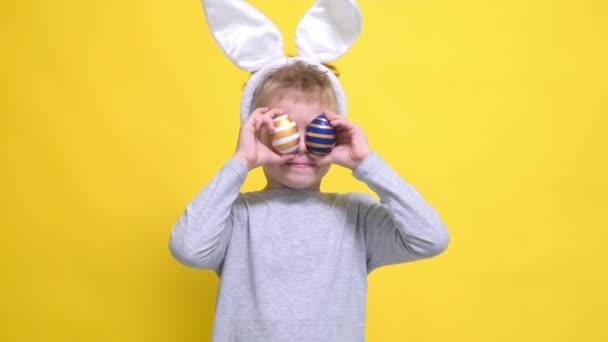 Portrétní velikonoční dítě. Chlapec v králičí králík uši na hlavě baví při pohledu do kamery vyčnívá jazyk dělat bláznivý legrační obličej s barevnými velikonoční vajíčka na jeho očích žluté ploutve studio pozadí