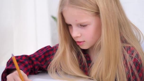 4k Blonďatá školačka, která doma studuje domácí úkoly. Školící knihy a zápisníky na stole. Vzdálenost učení on-line vzdělávání.
