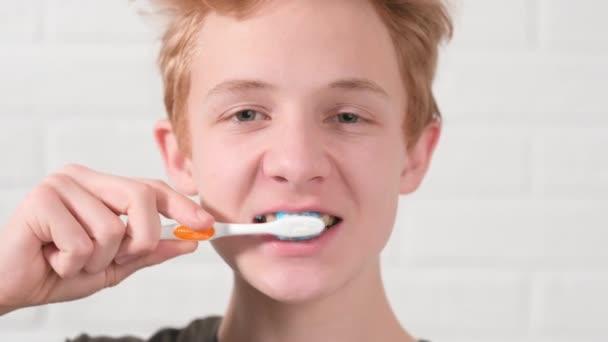 Portrét usmívající se červenovlasý dospívající chlapec s kartáčkem na zuby. Teenager kluk čistí zuby na bílém pozadí. Zdravotní péče, zubní hygiena