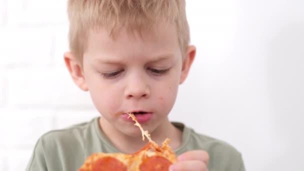 Portrait blonder Junge, der Käse Pizza Smiling aus nächster Nähe isst. Happy Child kaut Pizza in Scheiben. Ungesundes Junk-Fast Food