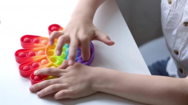 Dětská hra s pop to smyslové hračky. Chlapec tlačí na barevné duhové měkké silikonové bublinky. Stres a úleva od úzkosti. Trendy fidgeting hra pro stresované děti a dospělé.