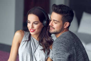 Happy young couple listening to music indoor with love