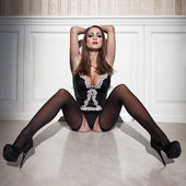 Sexy brunette woman in corset sit on floor at night