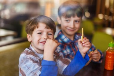 Little preschooler boys in fast food restaurant