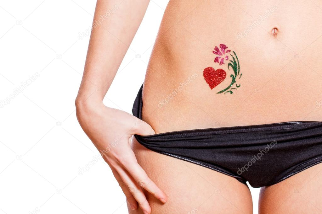 Woman with heart shaped glitter-tattoo isolated
