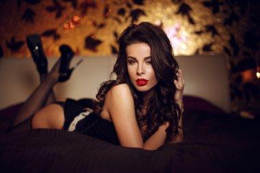 Sexy woman in black underwear posing on bed