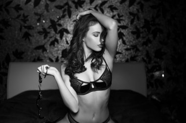 Sexy woman with handcuffs in bedroom black and white