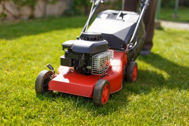 Pensioner mowing lawn with machine
