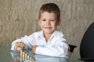 Little boy counting one euro coins in office