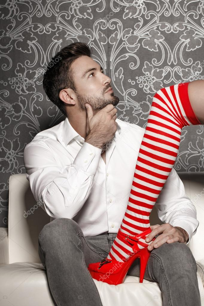 Woman in sexy christmas outfit trying seduce man on sofa