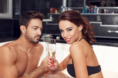 Young couple drinking champagne in jacuzzi