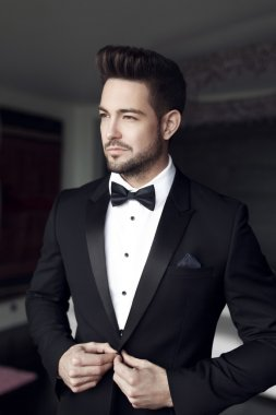 Sexy man celebrity in tuxedo indoor