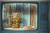 Banca di sottaceti, vodka e snack nella vecchia Tv, immagine nel sof
