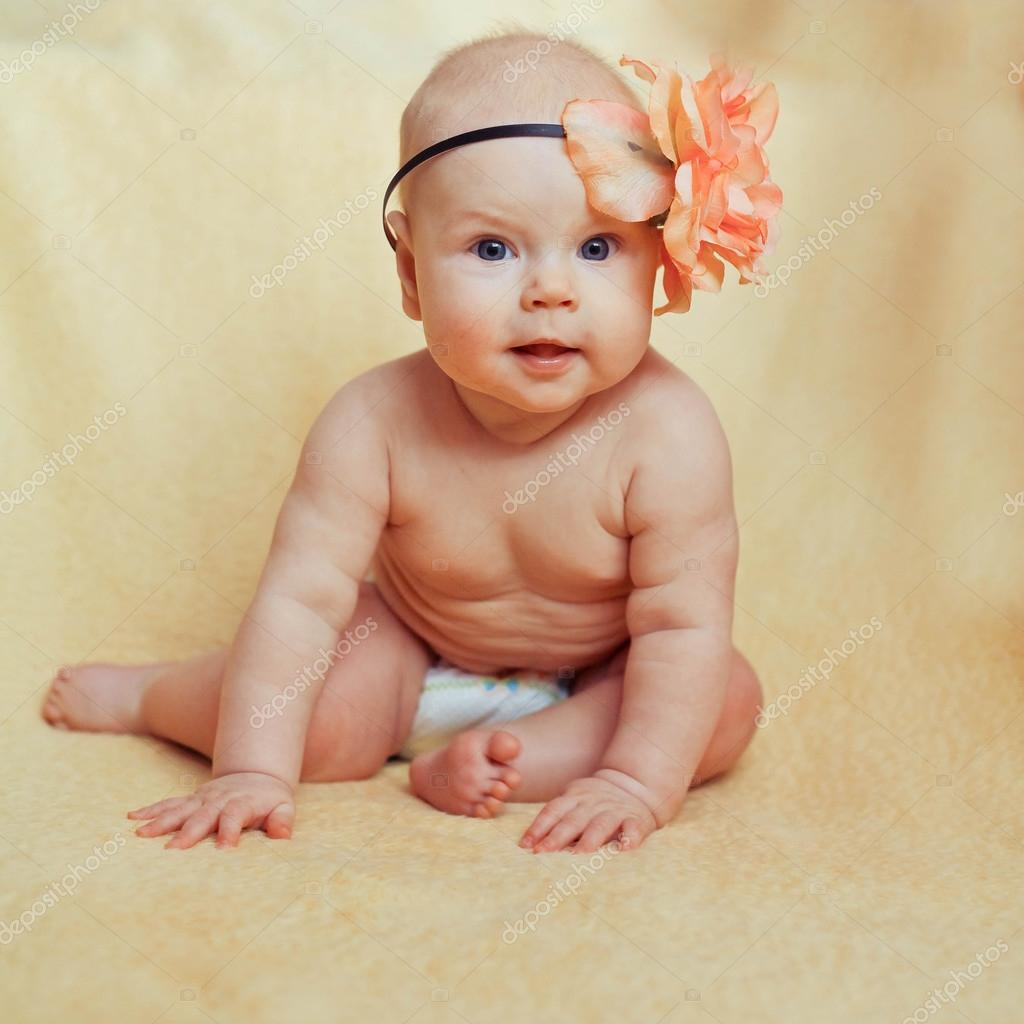 small cute baby girl with a adorable flower on head — stock photo