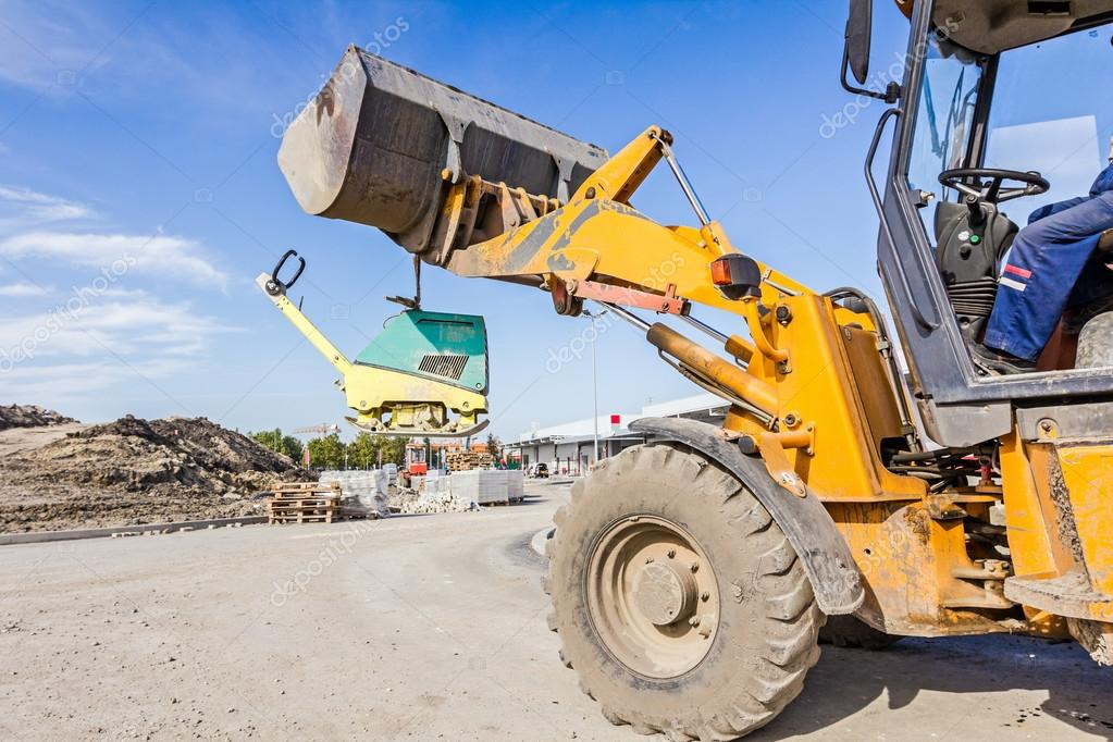 Moving vibration plate machine with excavator — Stock Photo