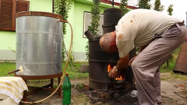 Az ember száraz ágakat dob egy házi készítésű szeszfőzde tűzdobozába, ami pálinkát, alkoholos italokat készít..