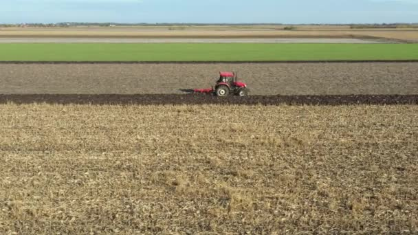 Dolly pohybující se výstřel jako paralelní následný traktor orá půdu na obdělaném zemědělském poli, připravuje půdu pro výsadbu nové plodiny příští sezónu.